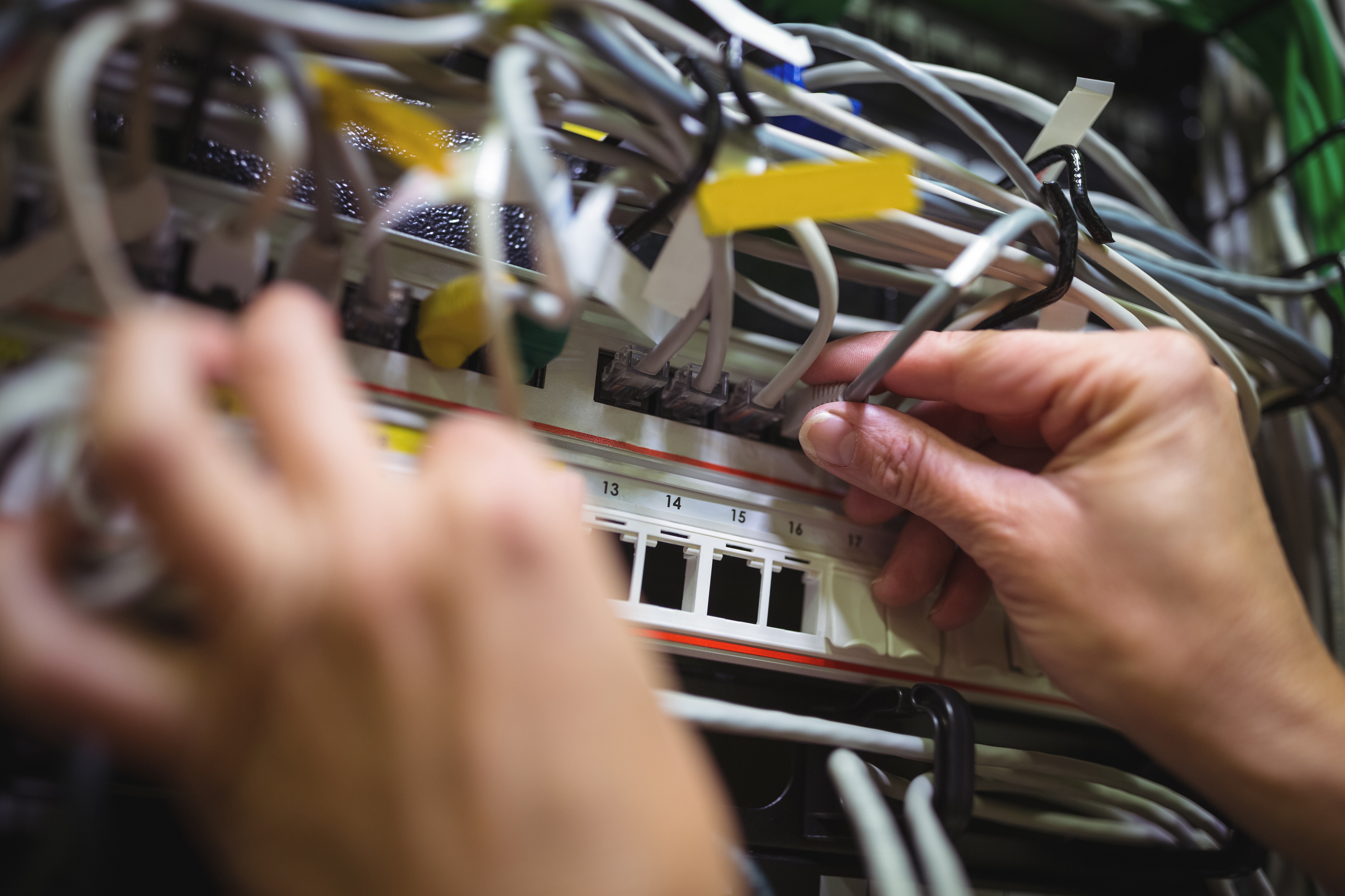 Technician plugging patch cable in a rack mounted server in server roo